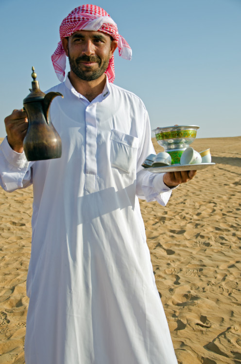 man serving Arabic coffee
