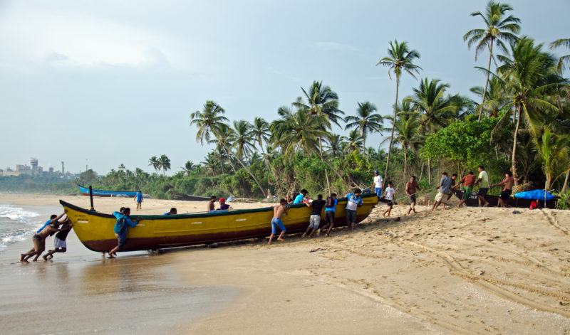 Fishermen pull in a boat